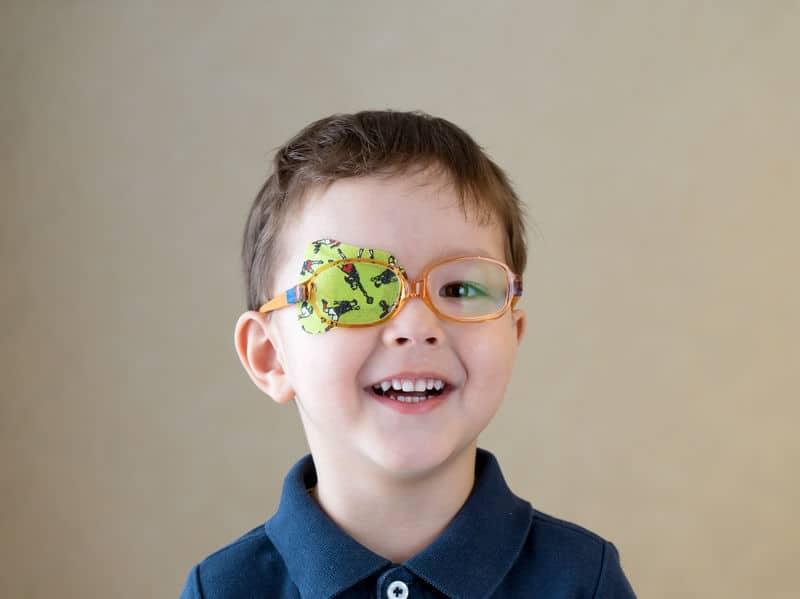 Menino com um dos olhos tampado e óculos laranja