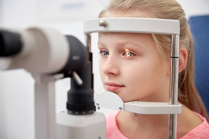 Menina loira fazendo exame de vista