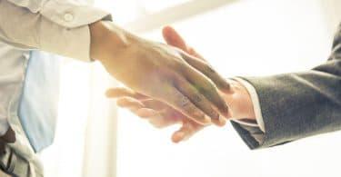 Aperto de mão entre duas pessoas.