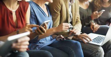 Pessoas sentadas usando celular e computador felizes