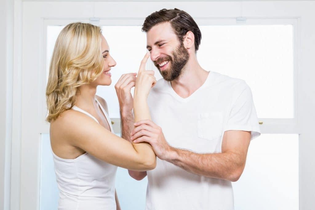 Casal de homem e mulher, ambos brancos e jovens, sorridentes, vestindo roupas brancas, trocando carícias e brincadeiras