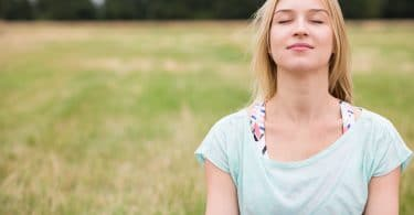 Mulher em foco de olhos fechados refletindo com grama ao fundo