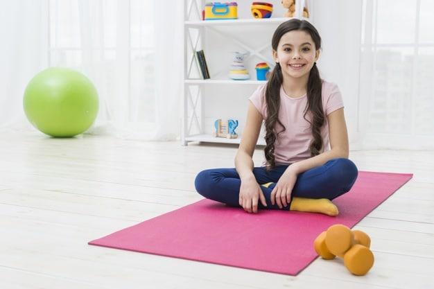 Criança sentada com as pernas cruzadas, em cima de um tapete de yoga.