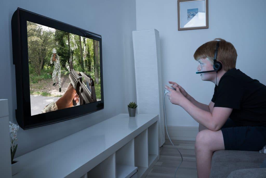menino jovem, sentado em um sofá, jogando vídeo game violento