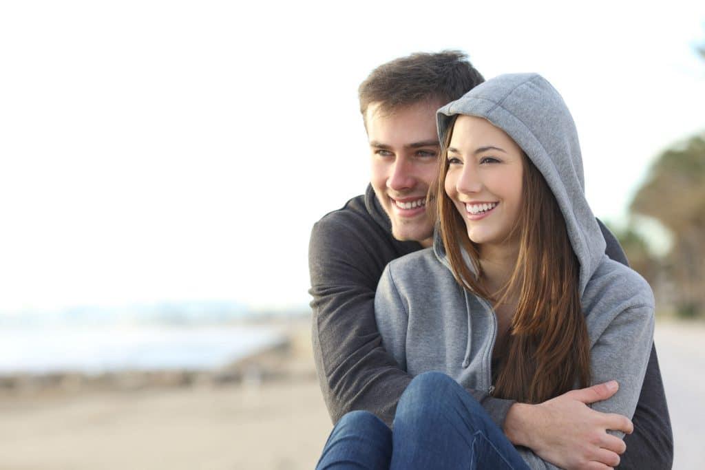 Dois adolescentes, homem e mulher, ambos brancos, vestindo blusas de moletom cinza e calça jeans, abraçados, sentados na areia de uma praia