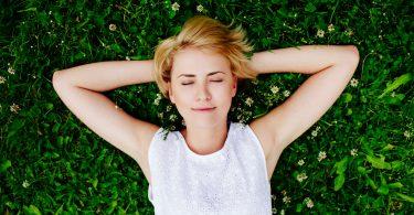 Foto de uma mulher deitada na grama sorrindo.
