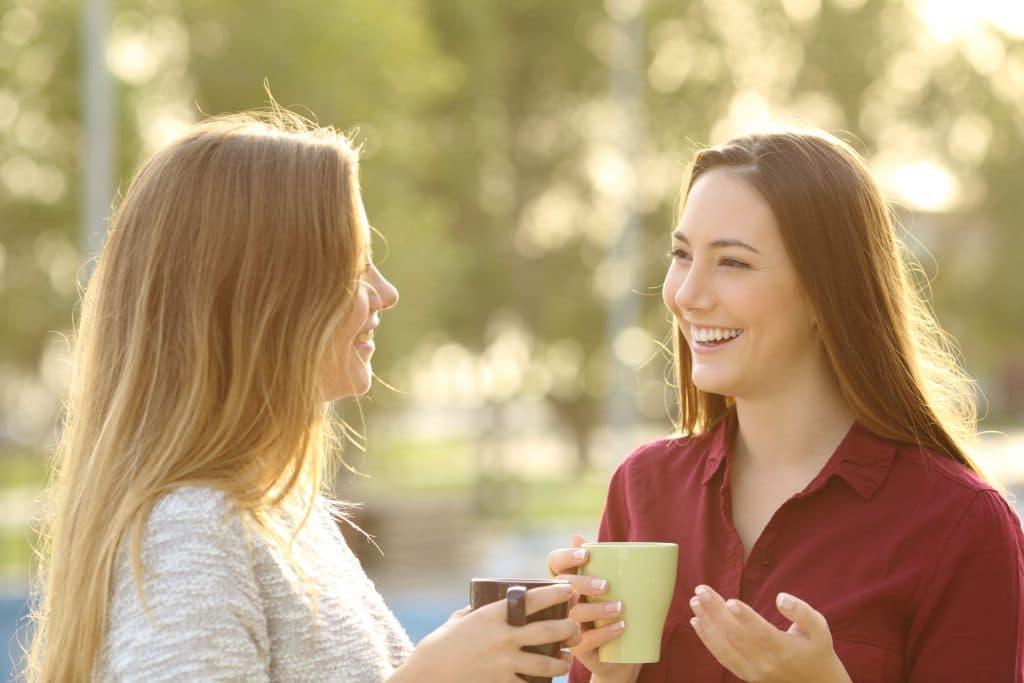 Duas mulheres jovens, sorridentes, tomando café em xícaras, conversando