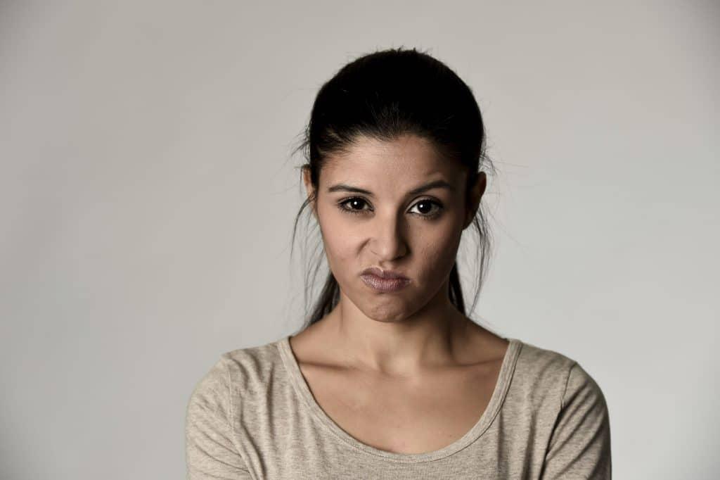Mulher parda com uma expressão de nojo, em pé, na frente de uma parede branca.