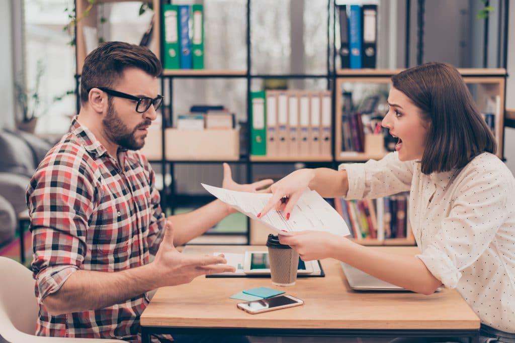 Homem e mulher, ambos sentados em mesa de escritório, discutindo de maneira acalorada. Mulher segura e aponta para um papel e gritando enquanto o homem está com uma expressão confusa.