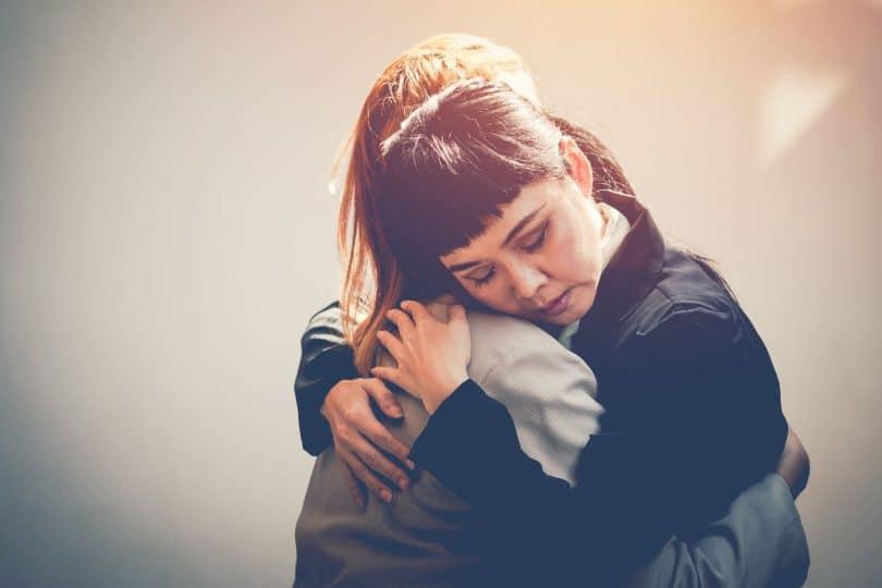 Duas mulheres se abraçando.