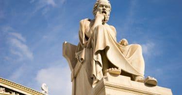 Escultura do filósofo Sócrates pensando sentado.