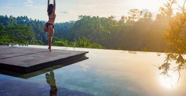 Retiro - Criatividade para reinventar sua vida Mulher fazendo yoga em cima de um pier de madeira em um lado, observando o nascer do sol.