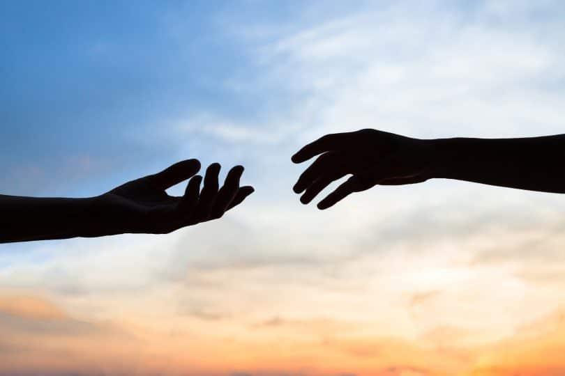 Duas mãos quase se tocando em frente ao céu.