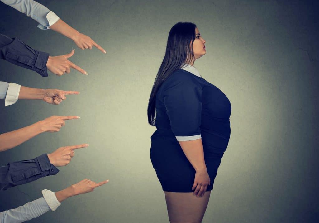 Mãos de várias pessoas apontando para uma mulher gorda