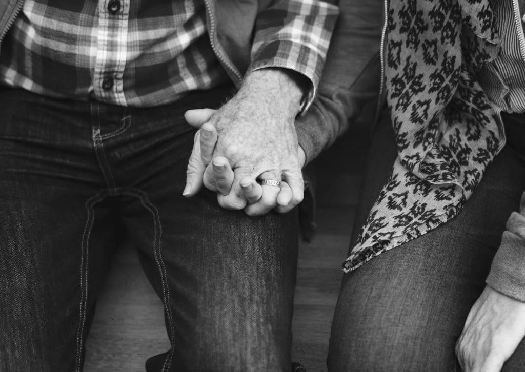 Foto preta e branca de casal de idosos sentados de mãos dadas