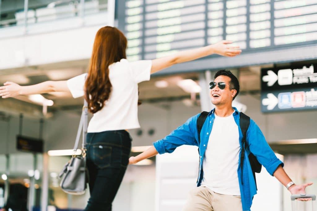 Homem e mulher, ambos asiáticos, felizes, correndo um em direção ao outro, se reencontrando em um aeroporto.
