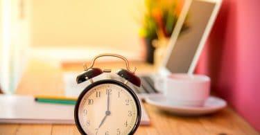 Relógio em uma mesa, em frente a um computador, papéis, caneca e alguns lápis.