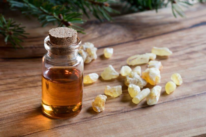 Vidrinho com óleo essencial de olíbano em cima de uma mesa com alguns cristais amarelos em volta.