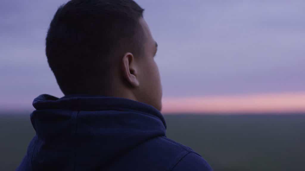 Homem de costas olhando para o horizonte.
