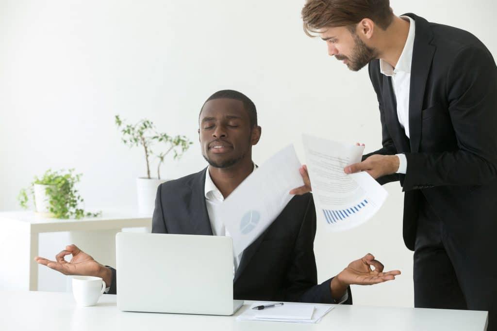 Homem negro, jovem, tranquilo, sentado em mesa de escritório, com os olhos fechados, com mãos em posição de meditação, ignorando homem brando que está de pé ao lado dele, gritando com vários papéis na mão.