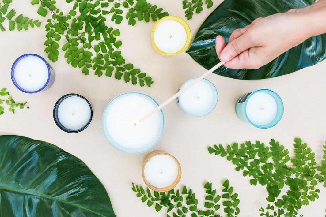 Mão acendendo velas de purificação vistas de cima com folhas