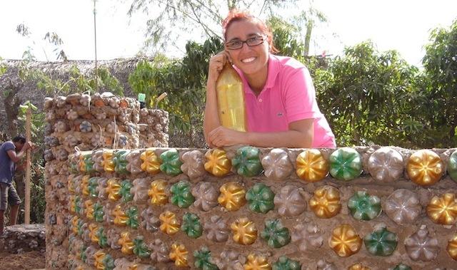 Ingrid com parede da casa feita de cimento e garrafas PET