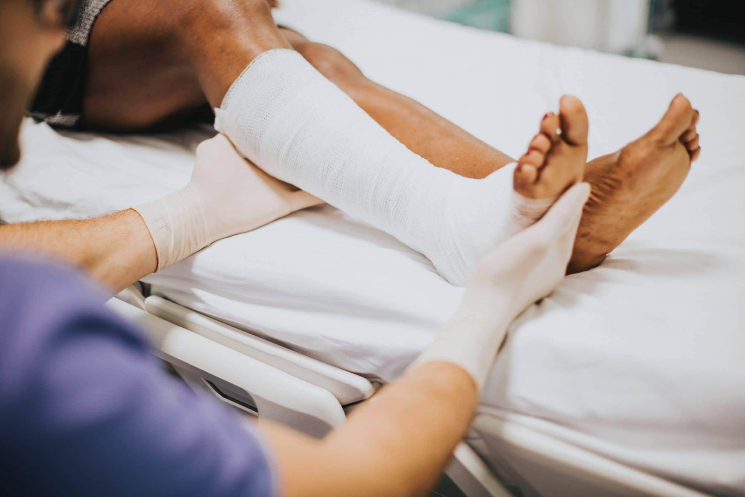 Enfermeira cuidando do pé engessado de um paciente.