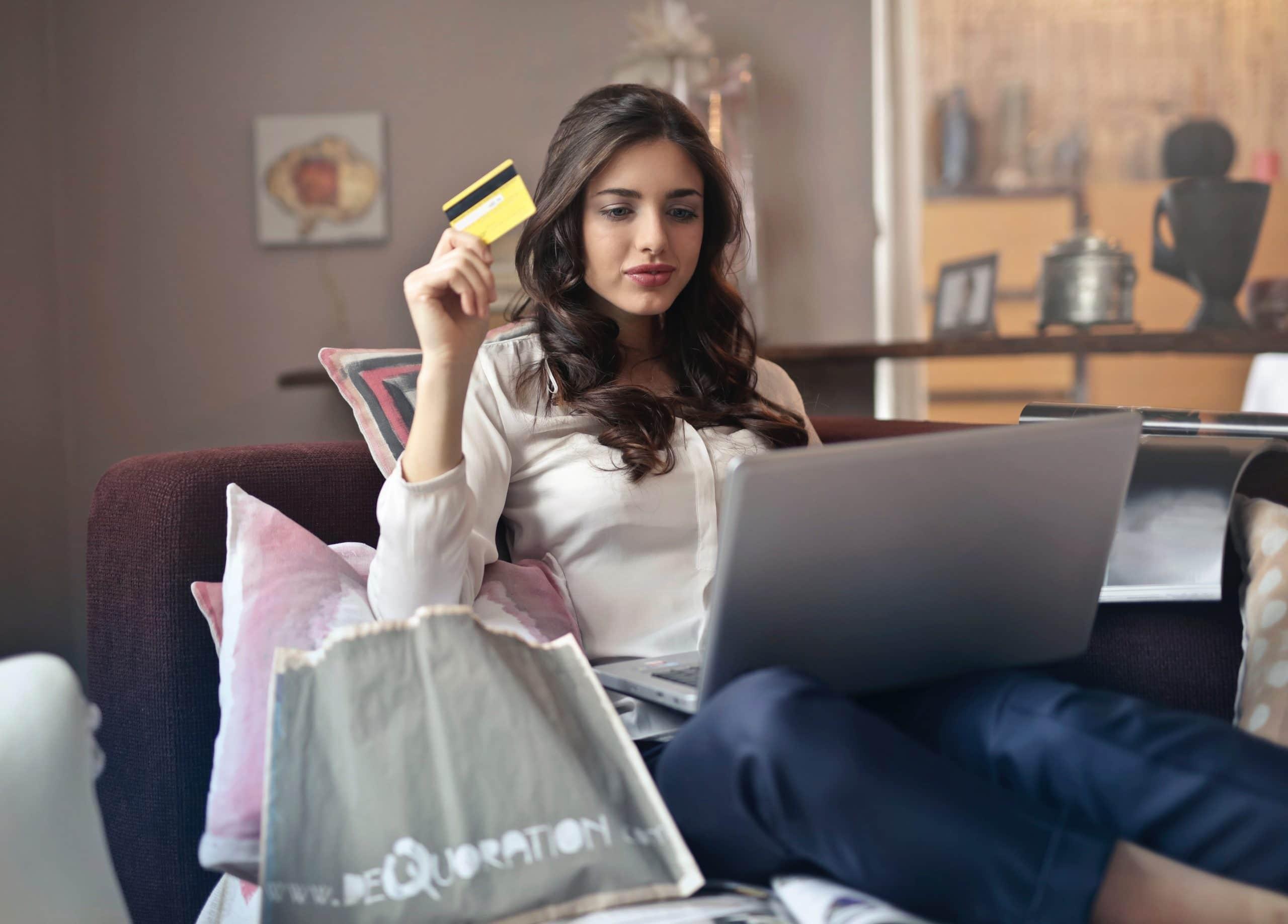 Mulher sentada no sofá com várias sacolas de compras, um computador no colo e um cartão de crédito na mão.