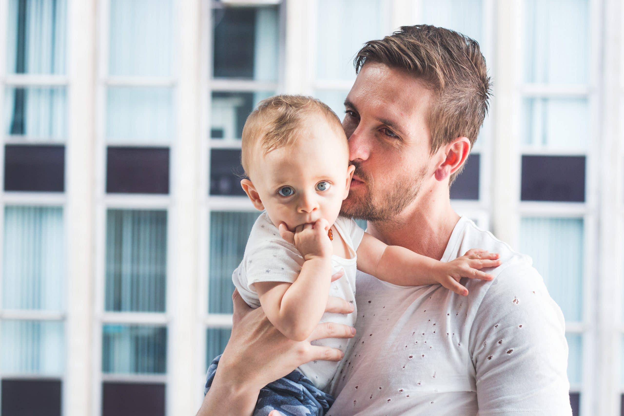 Pai segura criança no colo e dá um beijo em sua cabeça.