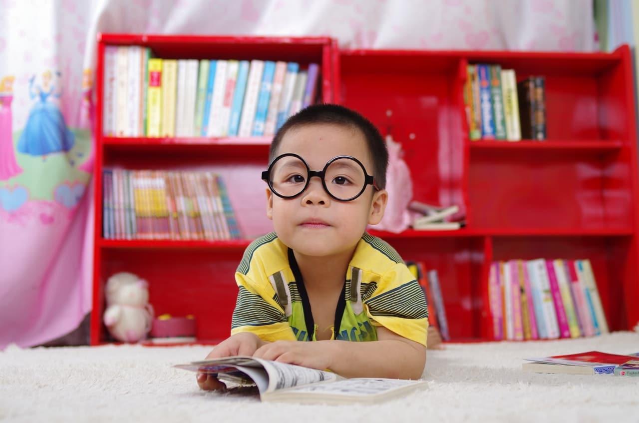 Menino pequeno de óculos apoiado em mesa com livro aberto olhando para a foto