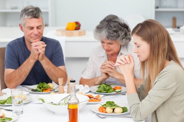 Família rezando na mesa em gesto de gratidão