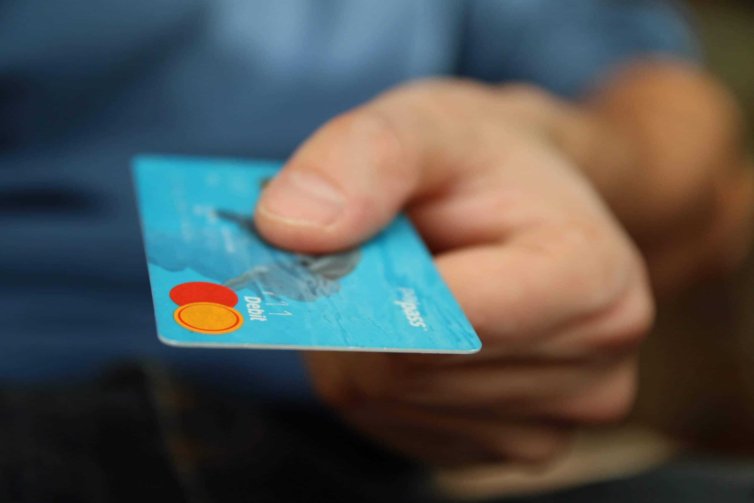 Homem segurando um cartão de débito azul.