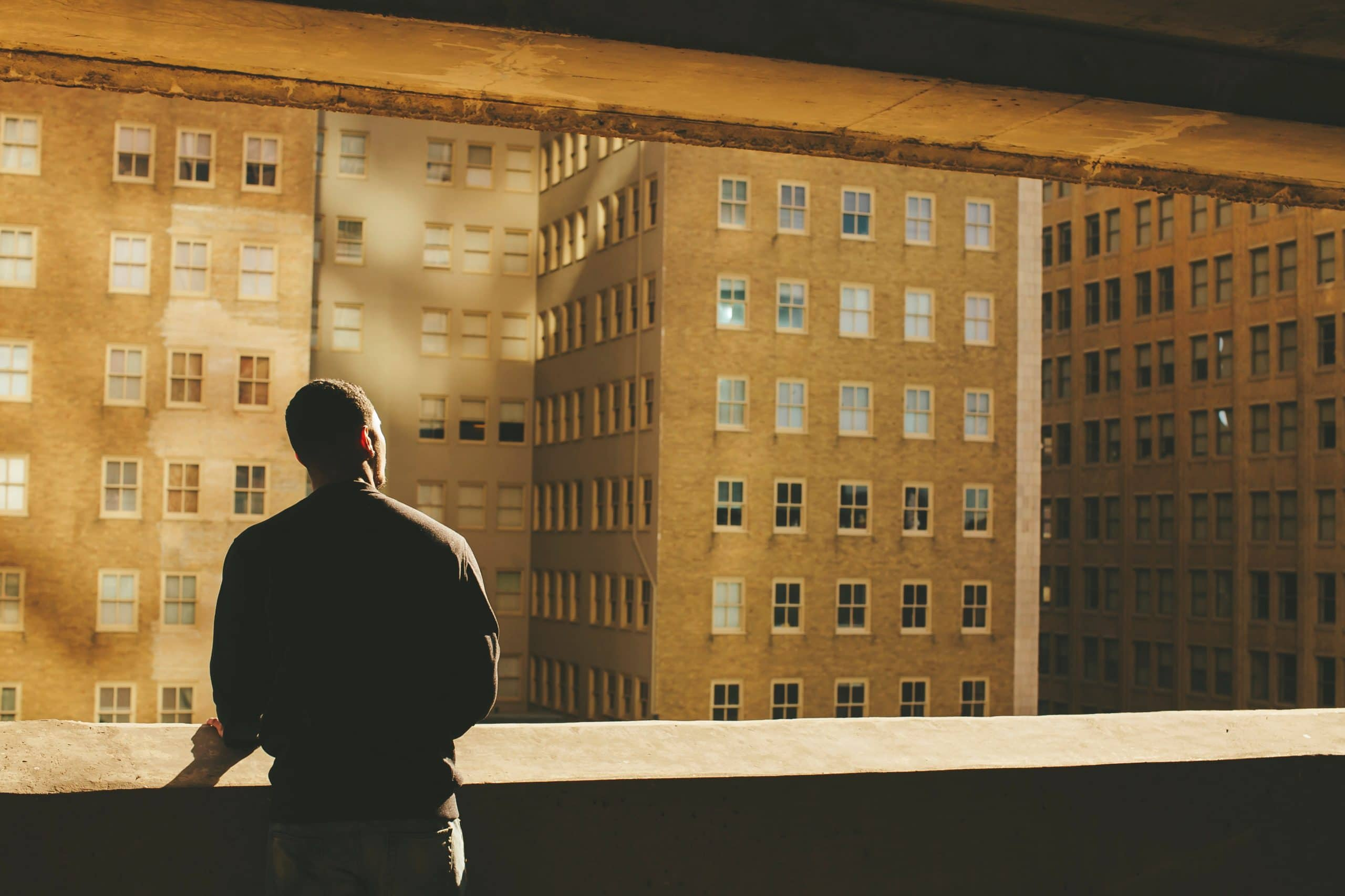 Homem pensando olhando para prédios pela janela.