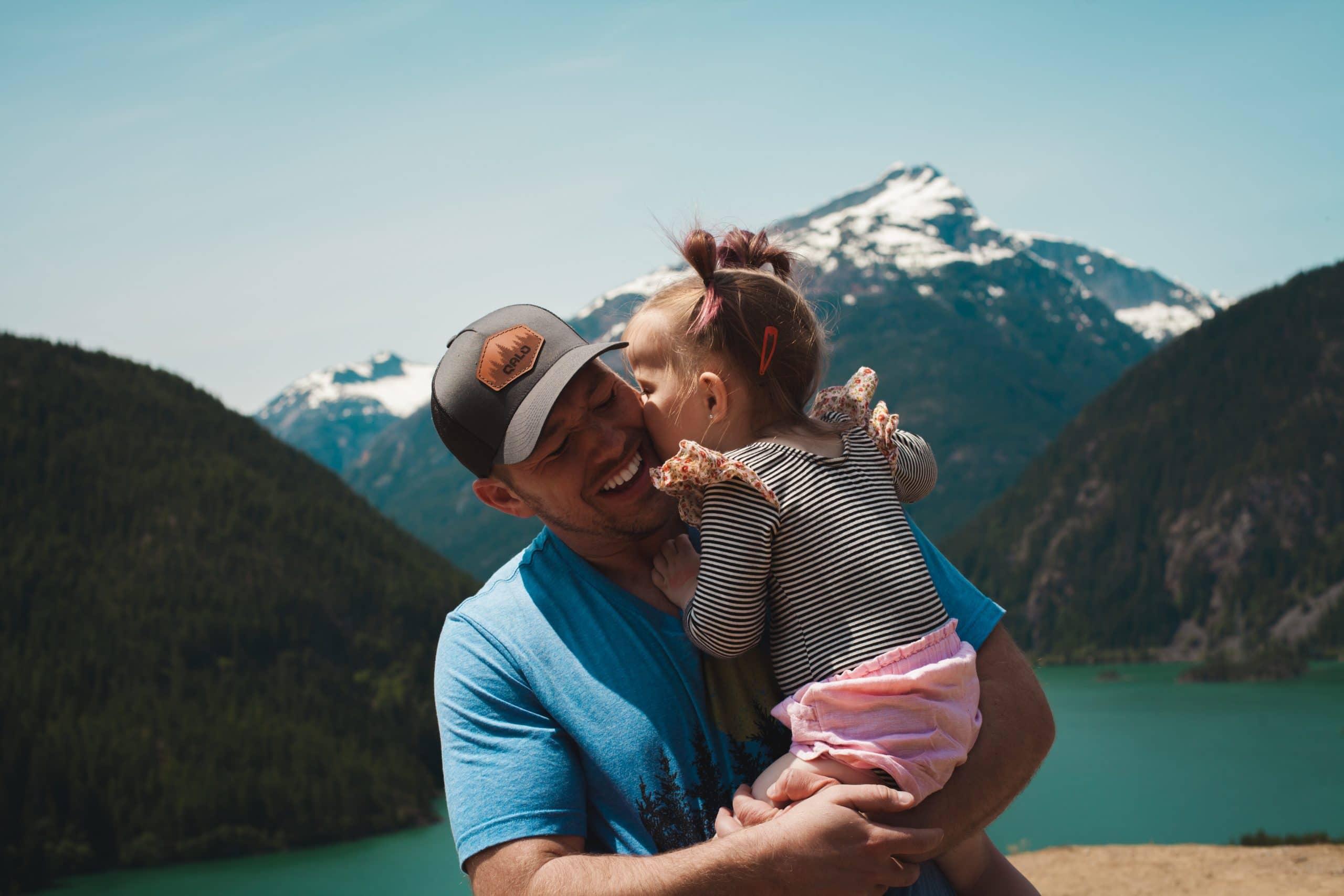 Pai segura sua filha no colo e ela lhe dá um beijo na bochecha. Ele sorri. Há uma montanha ao fundo.