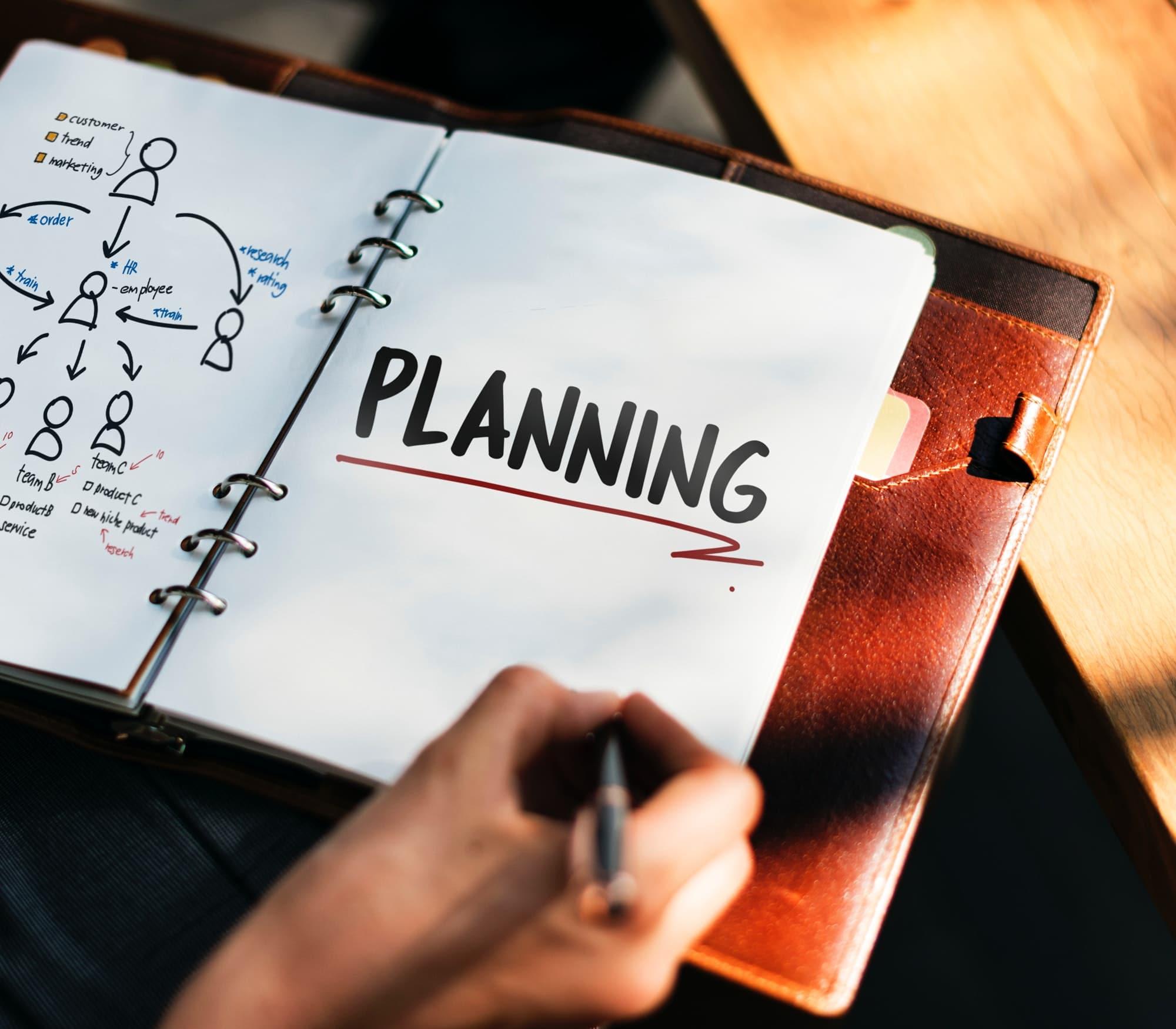"""Pessoa escrevendo """"planejamento"""" em inglês em um caderno em branco."""