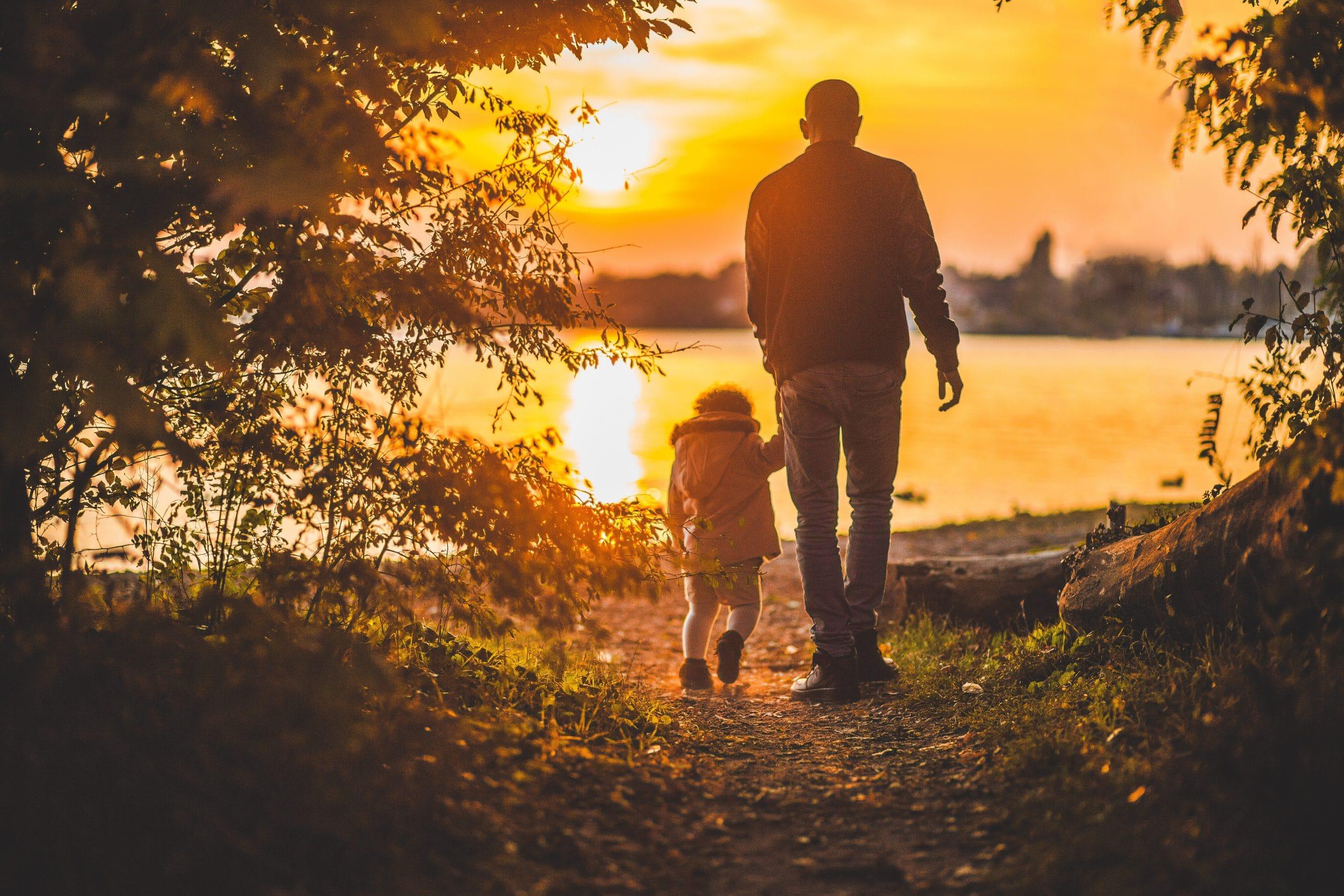Adulto segurando a mão de uma criança em um lugar cercado pela natureza em frente a um rio durante o pôr-do-sol.