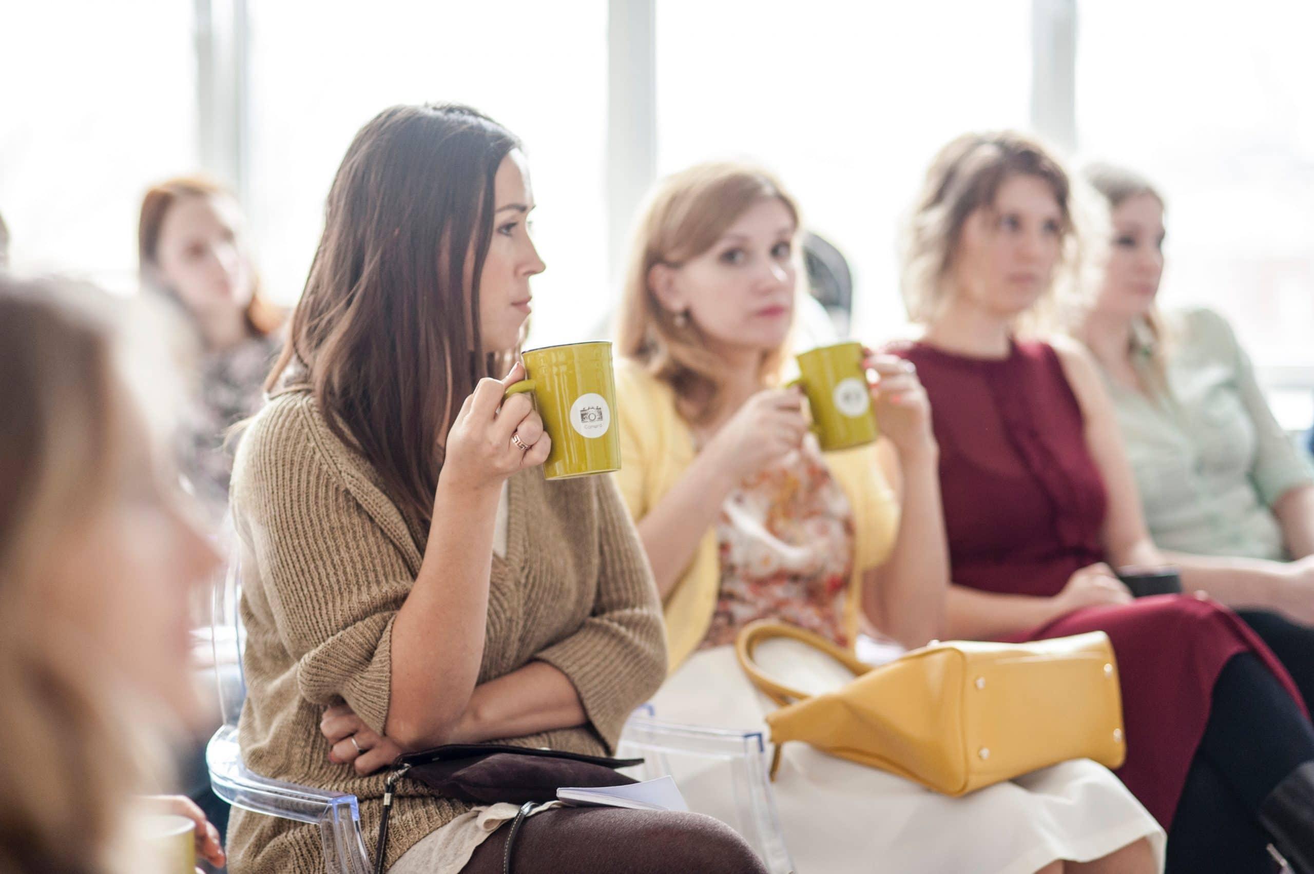 Mulheres sentadas em uma sala de espera, com copos personalizados nas mãos e rostos impacientes.