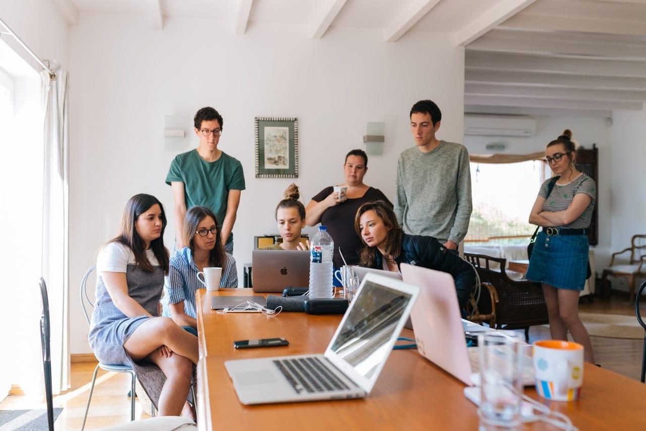 Jovens em reunião olhando todos para um computador
