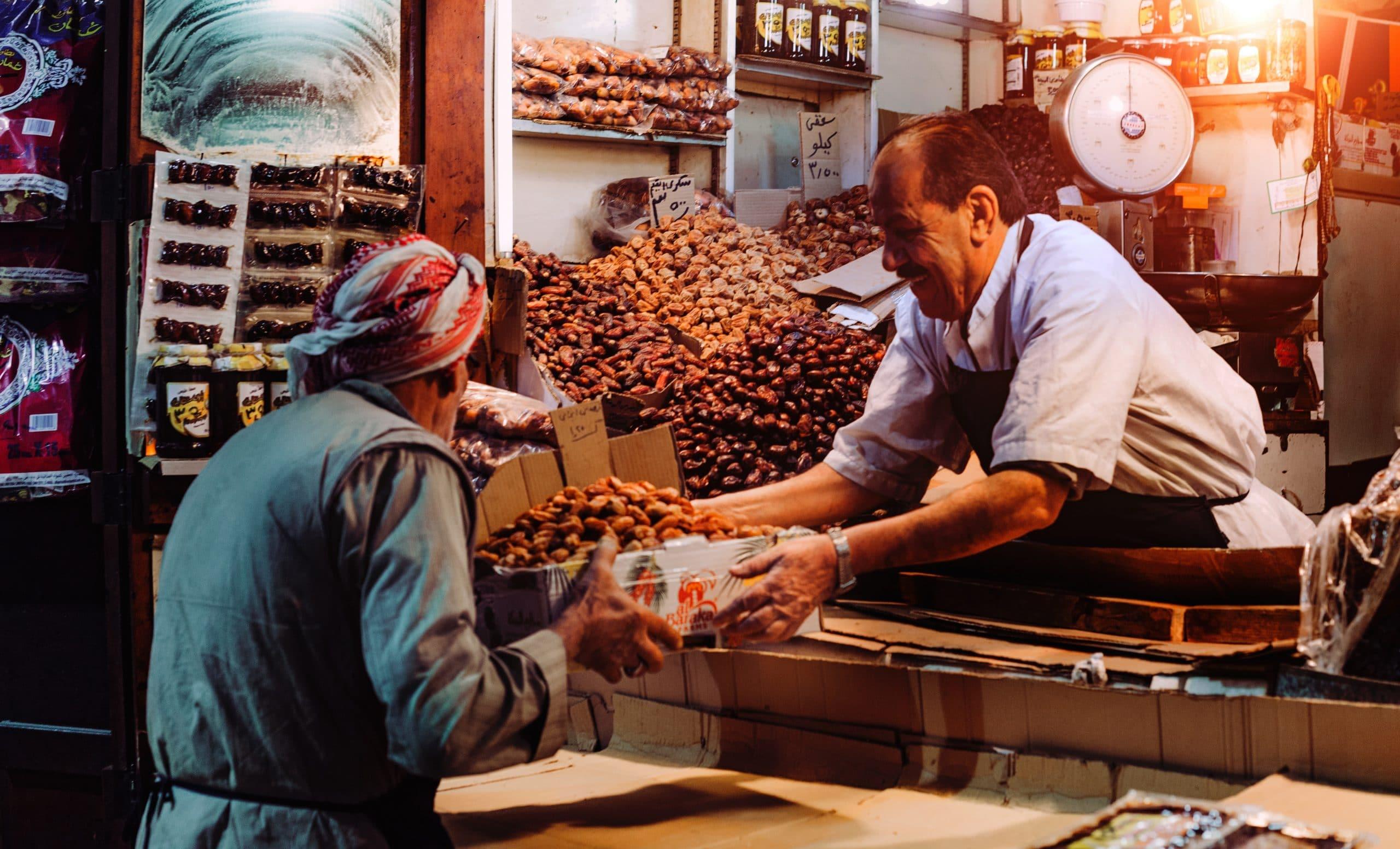 Feirante entregando uma caixa de frutas para um senhor na feira.