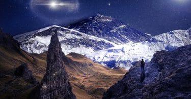 Homem no pico de montanhas nevadas, observando o brilho de um astro e das estrelas no céu.