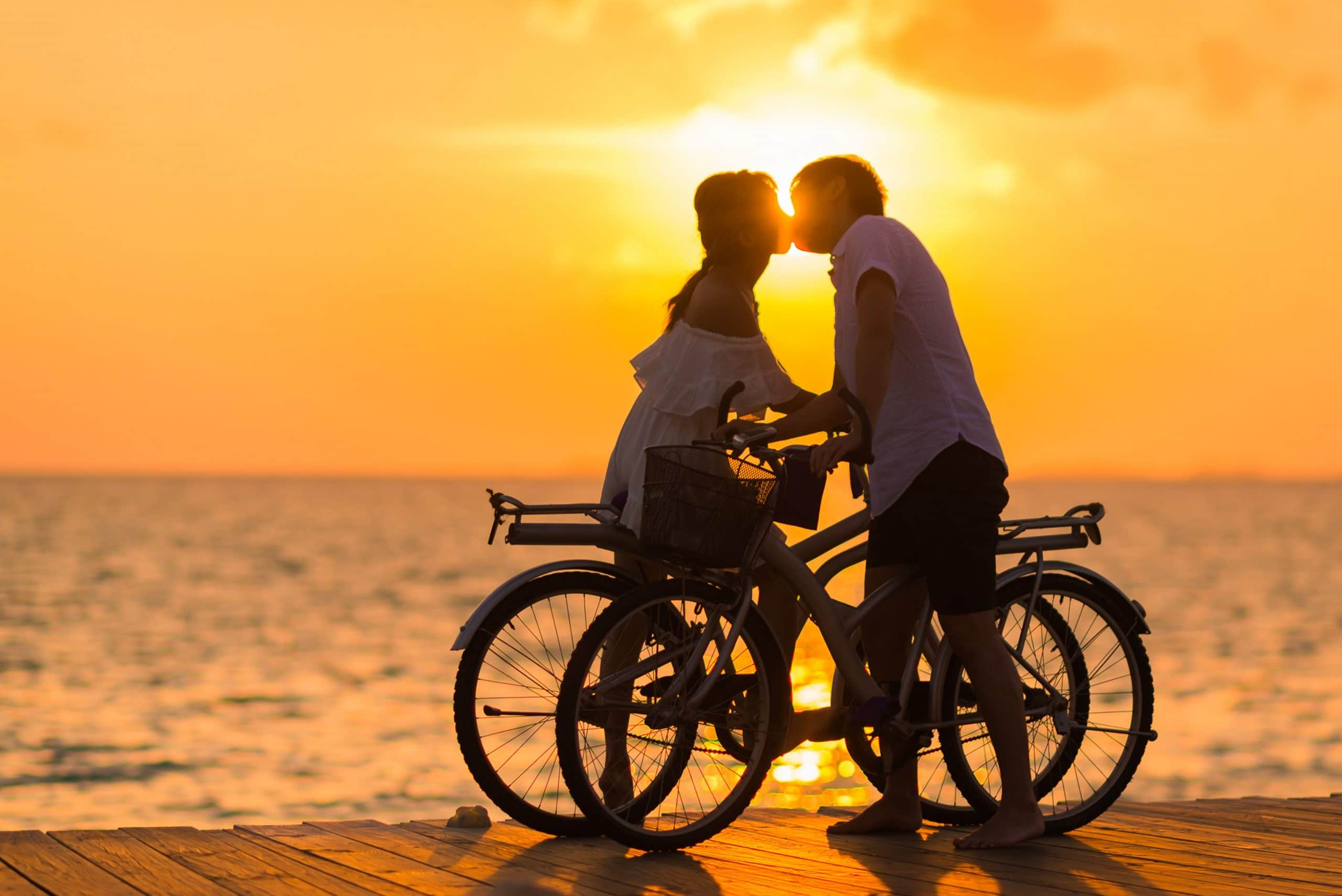 Casal de beijando em frente ao pôr-do-sol no mar. Ambos estão carregando suas bicicletas,