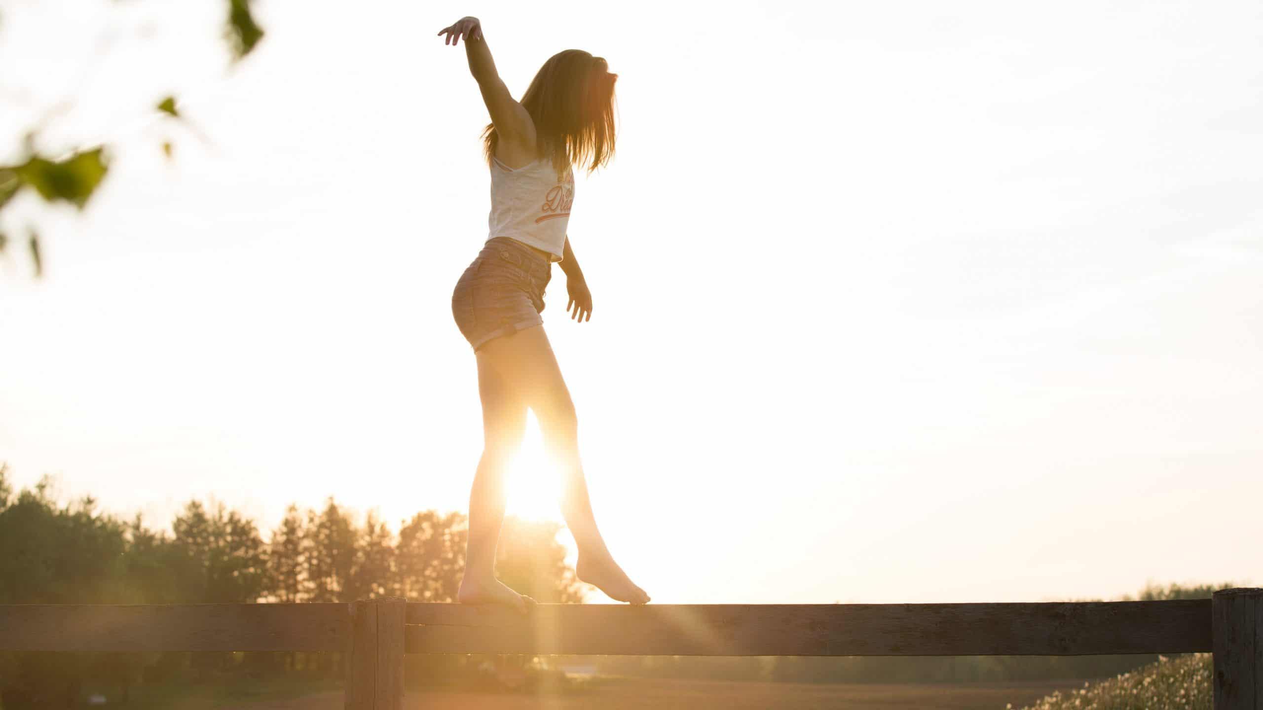 Menina se equilibrando em uma pequena mureta com o sol no horizonte.