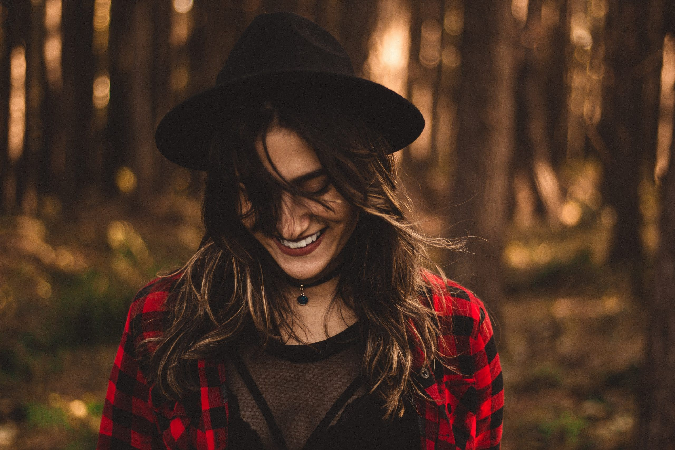 Mulher de chapéu com cabelos ao vento em foco com árvores ao fundo