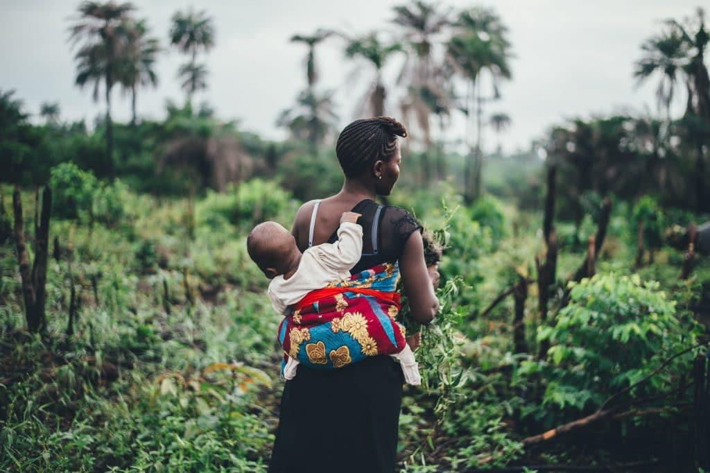 Mãe de costas carregando o seu filho em uma mochila no estilo canguru.