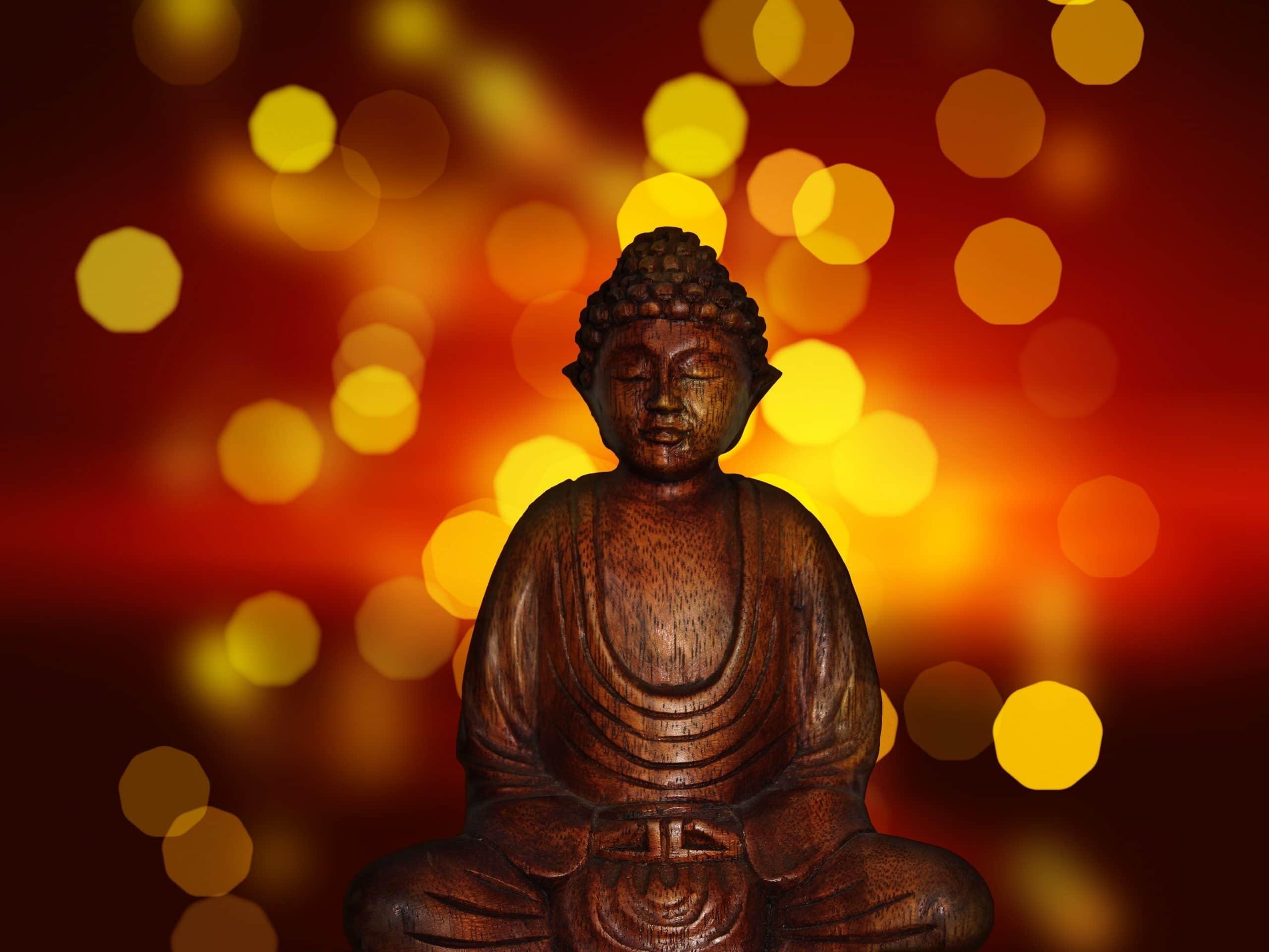 Escultura de Buda meditando em frente a um fundo iluminado.