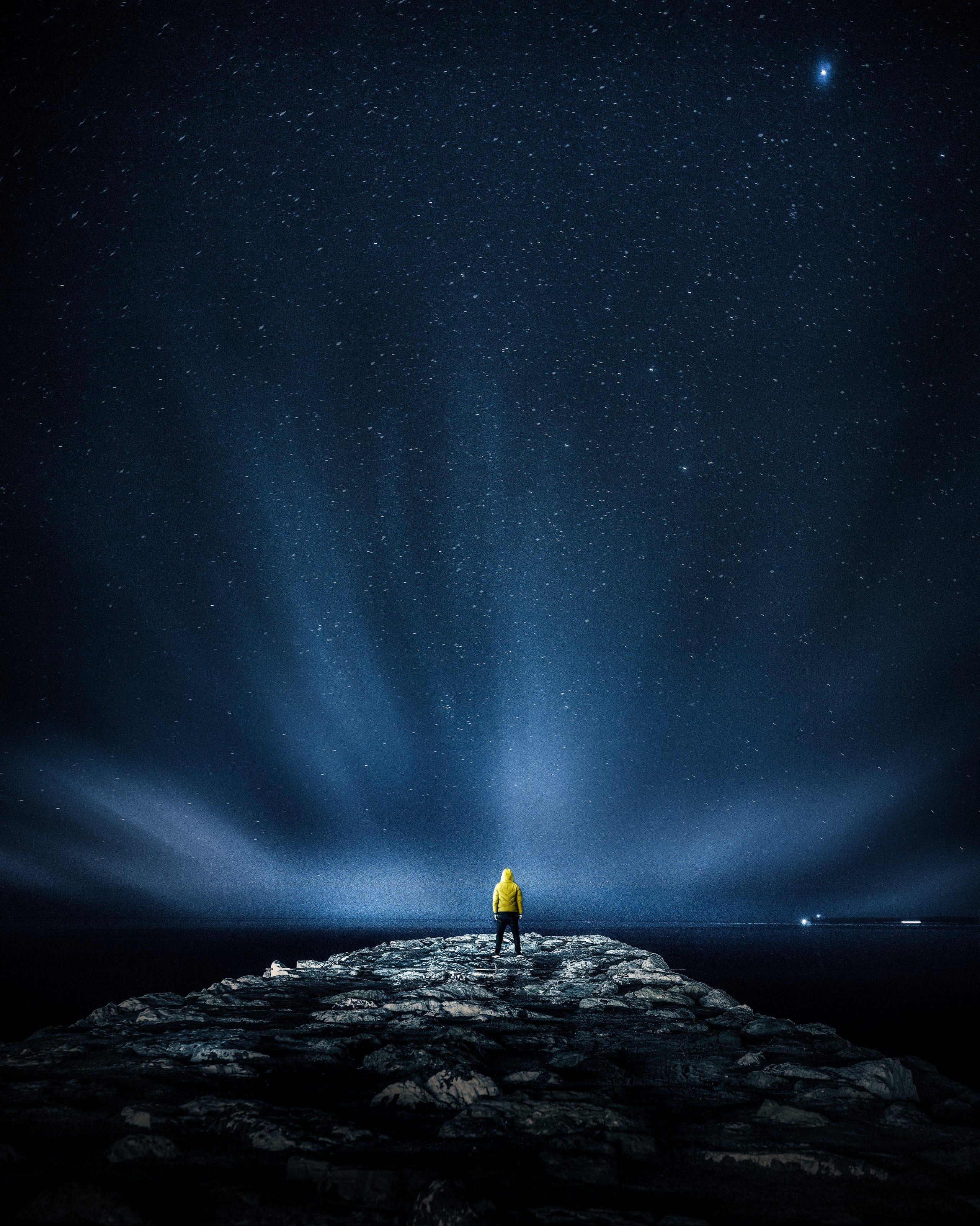 Homem em cima de pedras observando as estrelas e a imensidão do universo.