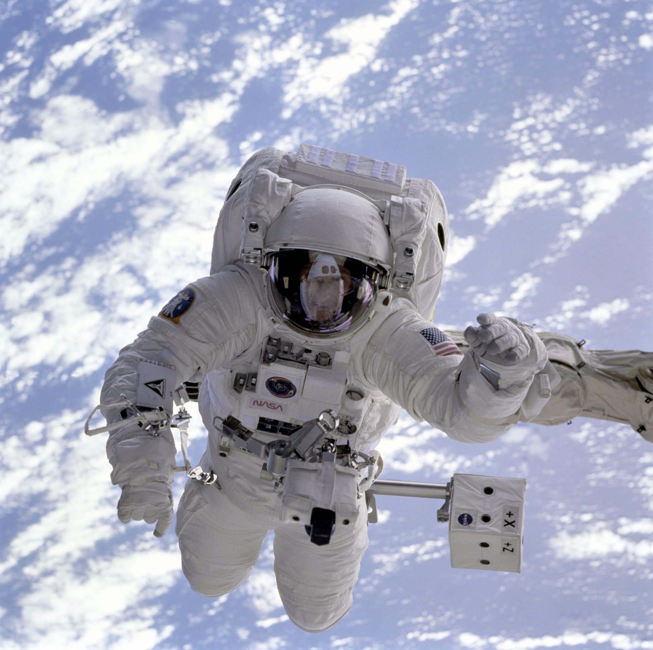 Astronauta flutuando no universo. Ao fundo é possível ver a atmosfera do planeta Terra.