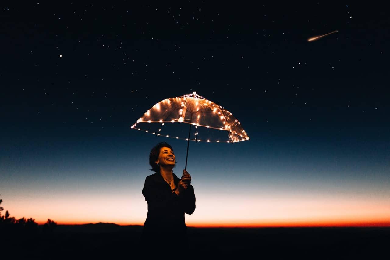 Mulher com guarda-chuva com luzes e céu escurecendo com estrelas ao fundo