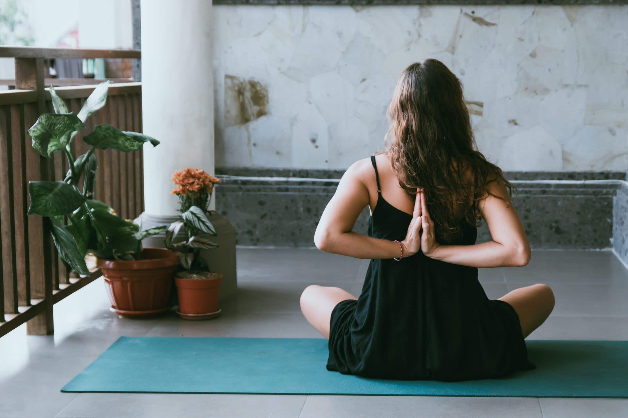 Mulher de costas em posição de meditação com braços nas costas sentada em tapete e plantas