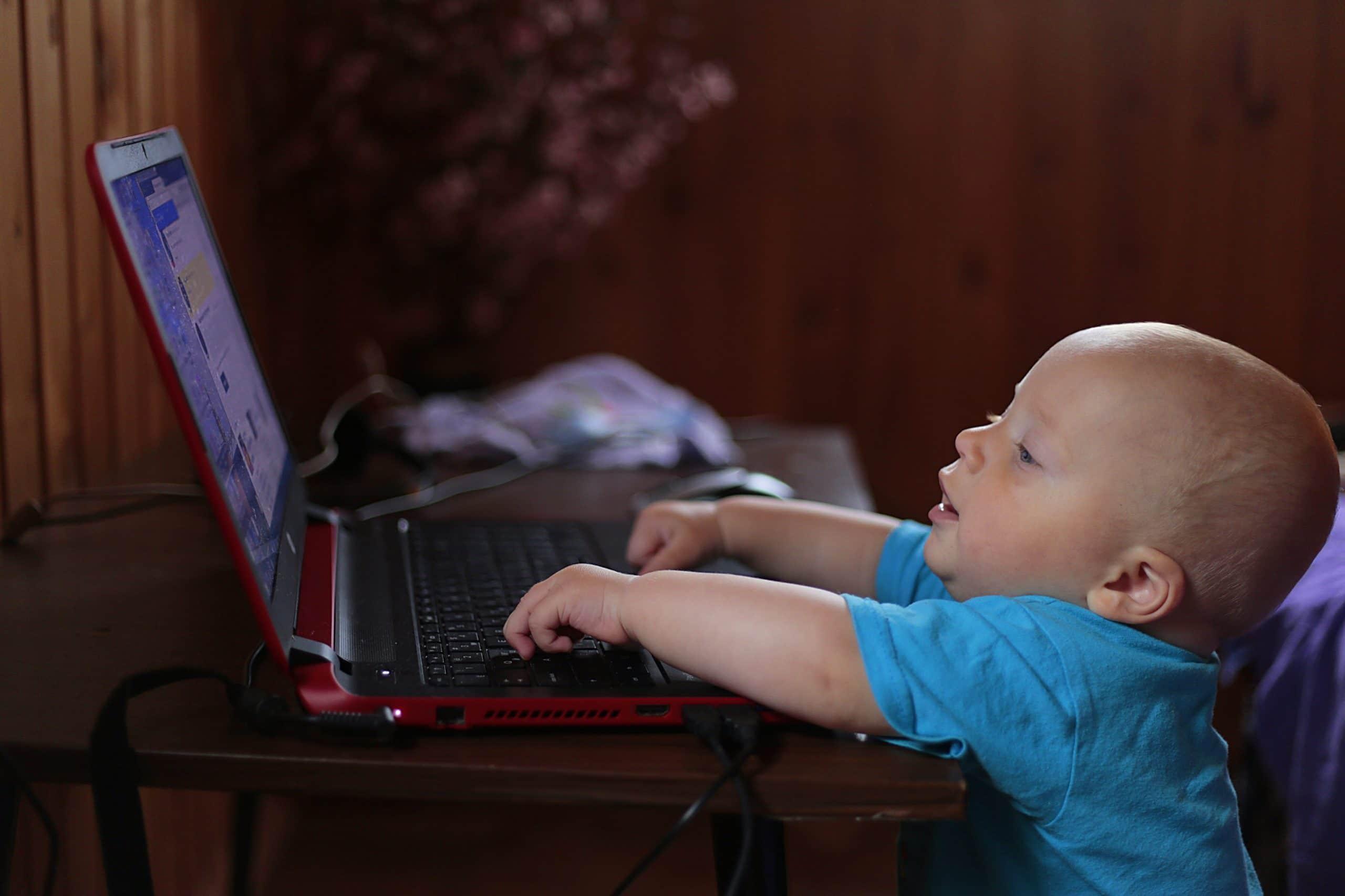 Bebê tentando digitar em um notebook.